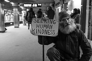 Homeless man with sign saying 'Seeking Human Kindness'