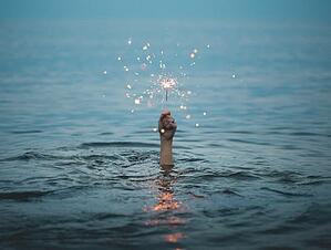 Hand in water holding a sparkler