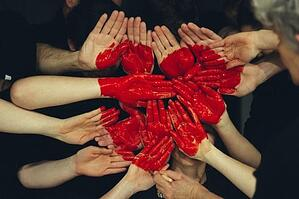 Collective hands painted with a red heart